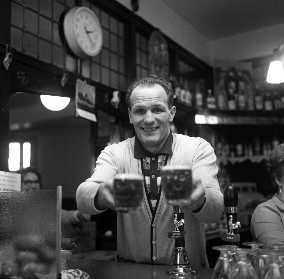 Henry Cooper behind the bar at the Fellowship Inn