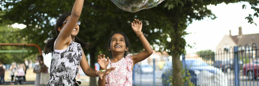 Two young girls reach to pop a large bubble