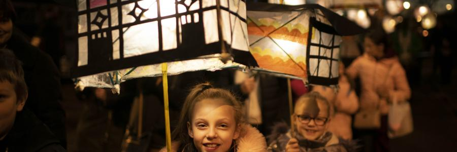 Photo of a young child carrying a lantern