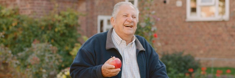 Phoenix resident Peter Lewis standing in his garden holding an apple that was grown there