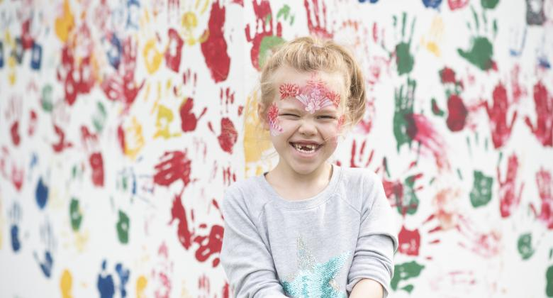 A small blonde girl with face paints smiles. The background is a white wall with painted hand prints on.
