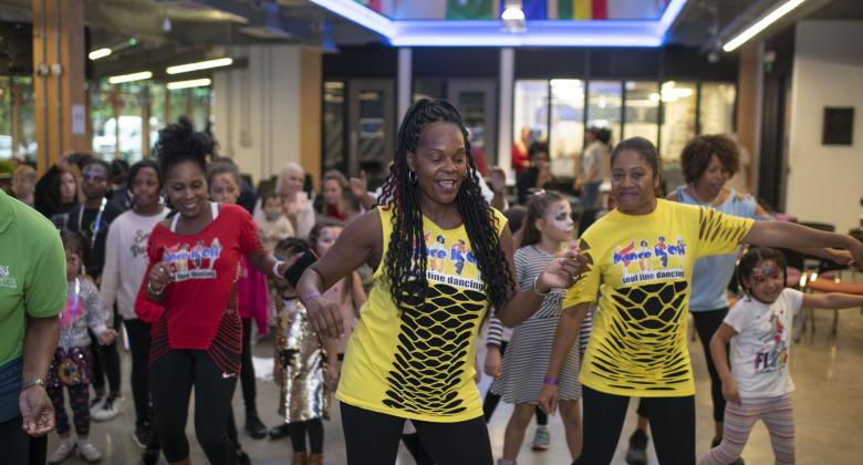 A group of people dancing wearing colourful t shirts