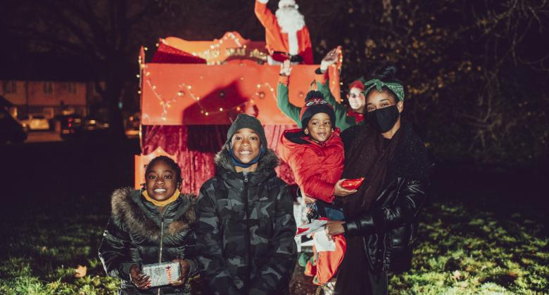 A family standing in front of Santa in his sleigh. Elves are standing in front of teh sleigh, behind the family and it is night time.