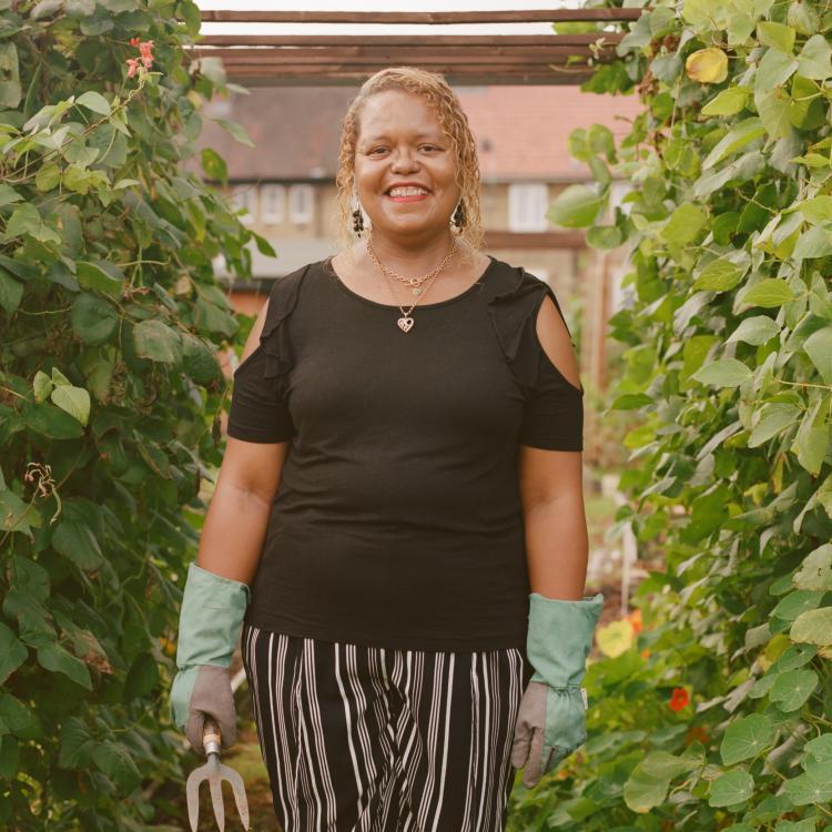 Joy Syahoui standing between two climbing plants in Farmstead Community Garden
