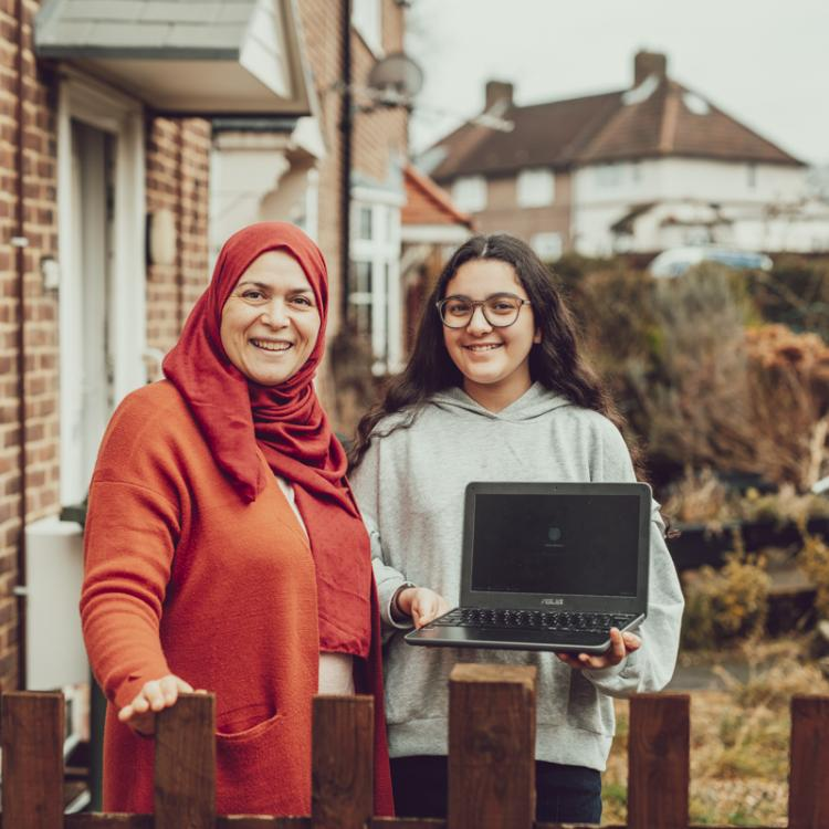 A mother and daughter stand in their front garden facing the camera and smiling. The young daughter is holding a silver laptop.