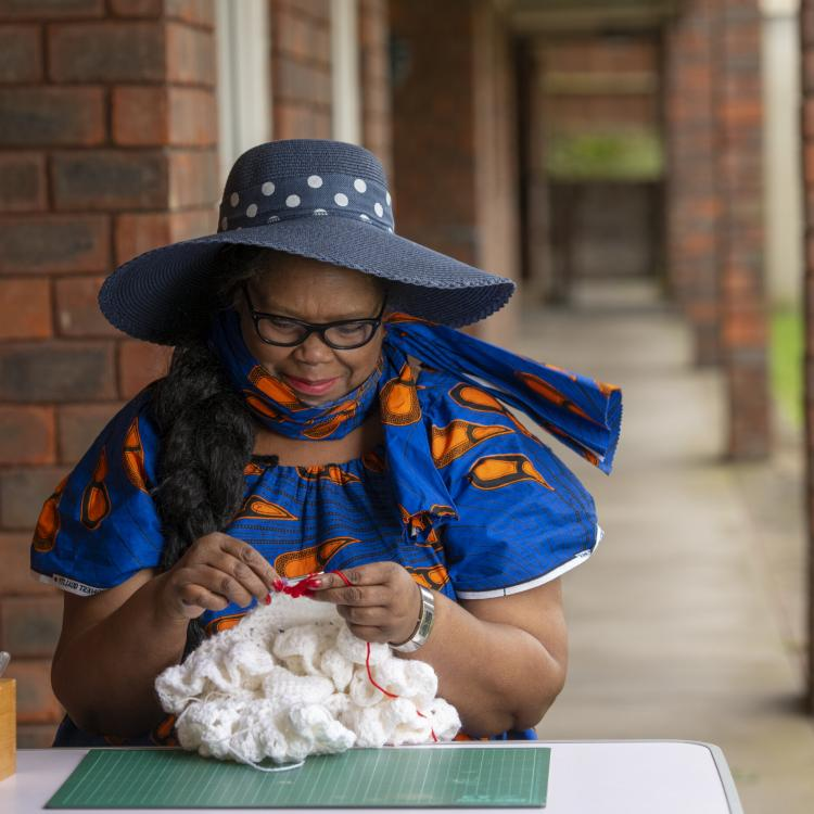 A lady wearing a hat, sits at a table doing crochet