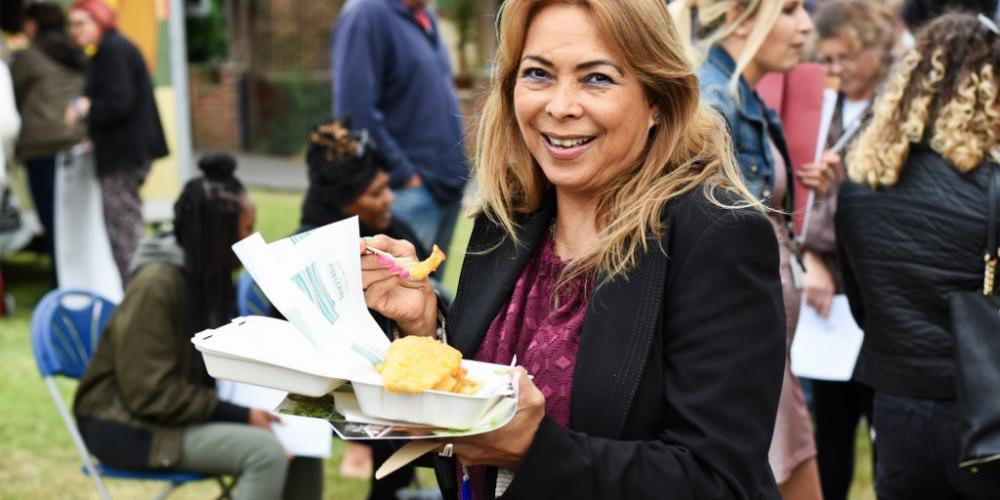 woman smiling holding fish and chips