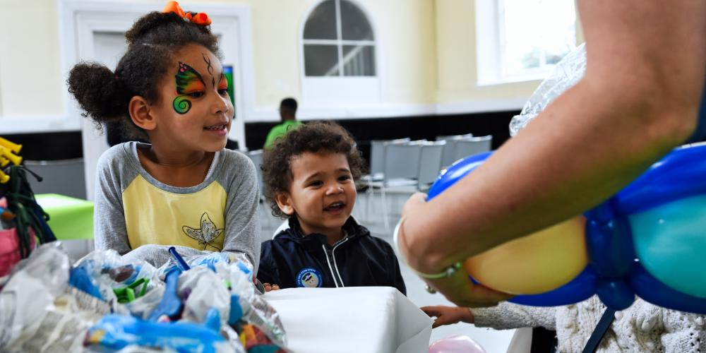 A young girl with face paint and her brother look at a lady making balloon sculptures