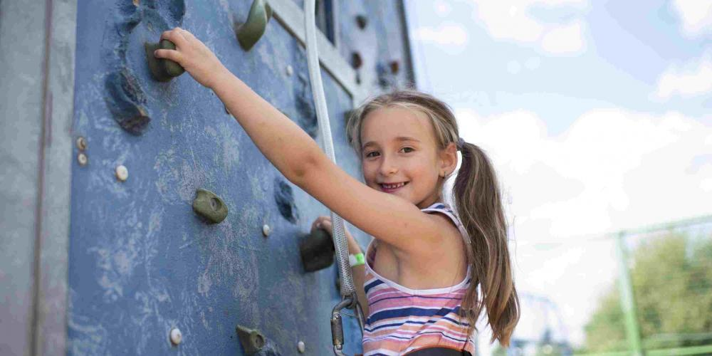 A young girl is on a climbing wall while smiling