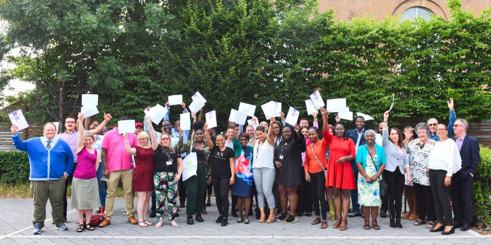 Group of graduates with their certificates and guests celebrating