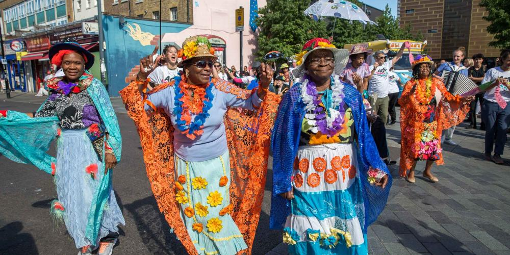 A group of ladies wearing colourful, cultural dress walk down the street as part of a parade