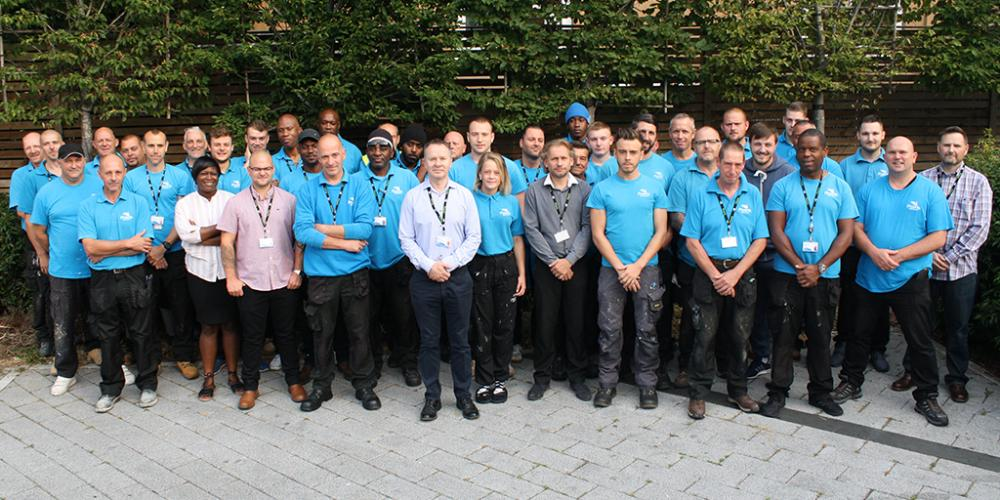 Group photo of PRS staff in branded blue t-shirts