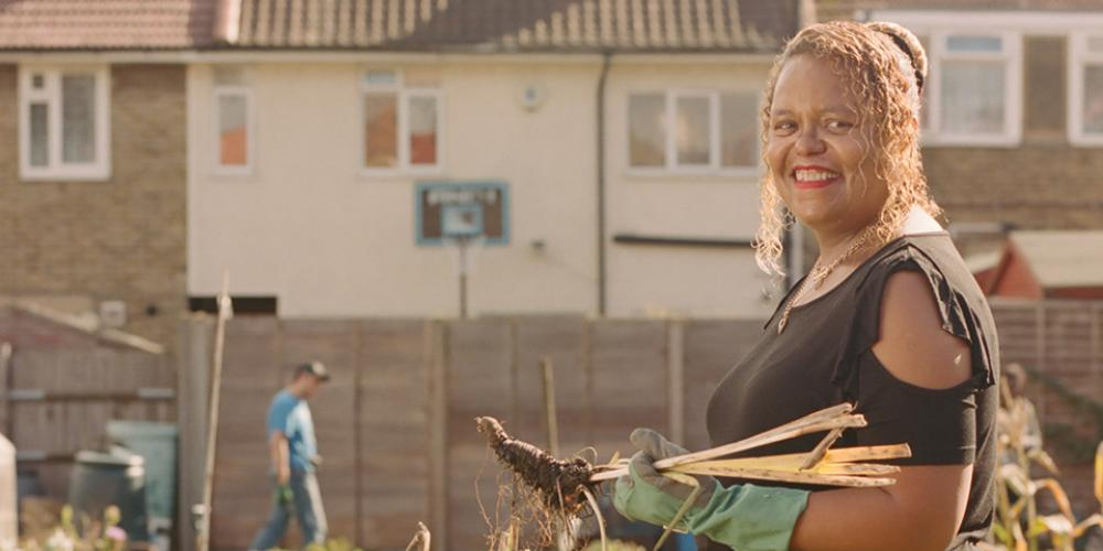 Phoenix resident Joy Syahoui standing next to a wheelbarrow in Farmstead Community Garden