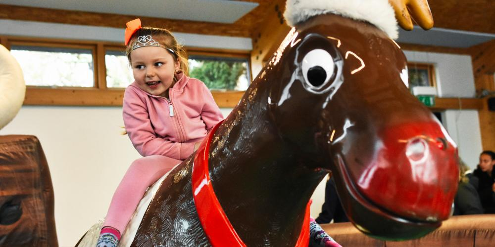 Photograph of a child enjoying the Rodeo Reindeer at Christmas Community Links