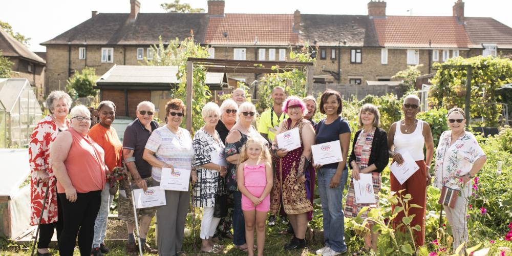 Phoenix in bloom gardeners at their prize giving, looking happy with certificates