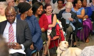Photo of Kim Canagasabey and her guide dog Jemma at Phoenix Community Housing's annual general meeting