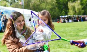 Photo of mother and daughter enjoying a large bubble at a fun day