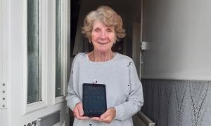 A lady standing in her front door way, smiling while holding a computer tablet device