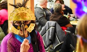 A Phoenix resident holding a mask that she has made in front of her face, surrounded my other residents working on their own masks