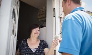 Photo of a member of the Phoenix Repairs Service entering a home