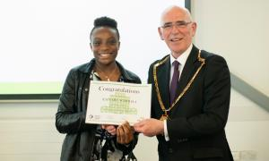 Photo of the Phoenix Academy's youngest graduate, Zainab, with then-Chartered Institute of Housing president Jim Strang