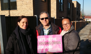 Photo of Jim Ripley and others holding up a board reading Fix The Housing Crisis