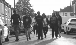 A blakc and white photo of a group of young people walking down the street. They are smiling and laughing